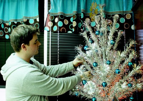 "Senior Wade Henderson decorates a Christmas tree in his third hour class. Business teacher Bethany Siegel allowed Henderson to decorate the classroom tree to uplift her Christmas spirit. ""Decorating gets me in the Christmas spirit,"" Siegel said."