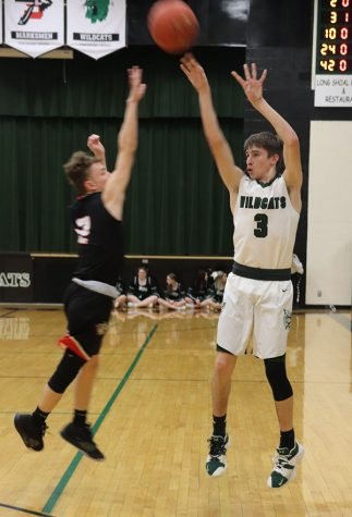 Junior point guard Trey Palmer shoots a three pointer during the Courtwarming game against El Dorado Springs on Feb.7. Varsity won 56-53.