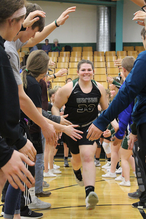 Freshman Ashley Spry runs through the tunnel of pep club members at home game. Spry has had to step up due to lack of upperclassmen players.