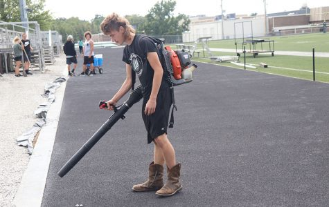 Sophomore Sean Owens uses a leaf blower to remove rocks from the newly surfaced track. PE classes helped prepare the track for paint.