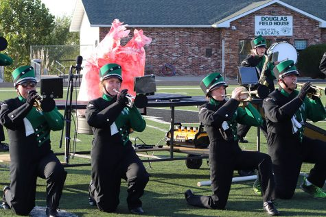 """Freshmen Alison Williston, Alyson Alcantara and sophomore Summer McCanon take a knee while preforming the trumpet feature during the fourth movement of the """"Elemental of fire Field show."""