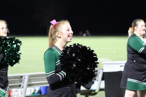 Junior Kaylee Lawson shouts a cheer for a home football game against Skyline for there pink out theme