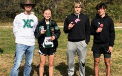 Cross Country head coach Ehren Banfield, junior Alyssa Alcantara, senior Trey Palmer and sophomore George Montez gather for a celebratory photo after qualifying for state at the Hermitage District meet on Oct. 31. Alcantara placed sixth, Palmer placed fifth and Montez placed sixth. All three will be running at the state meet on Nov. 5 in Columbia.