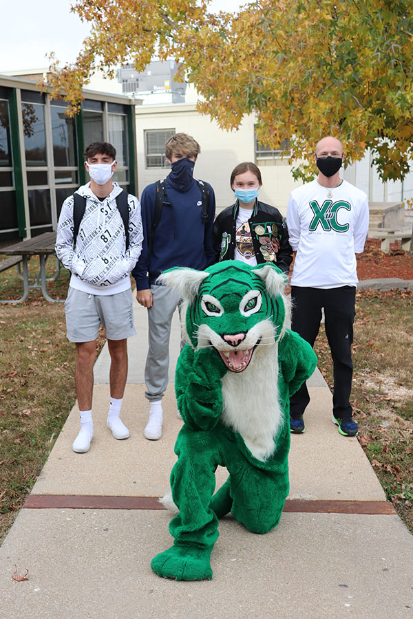 Sophomore George Montez, senior Trey Palmer, junior Alyssa Alcantara and head coach Ehren Banfield gather for a picture with Wally the Wildcat after the cross country state walk. The State Cross Country meet was held Nov. 5-7 at the Gans Creek Cross Country Course.