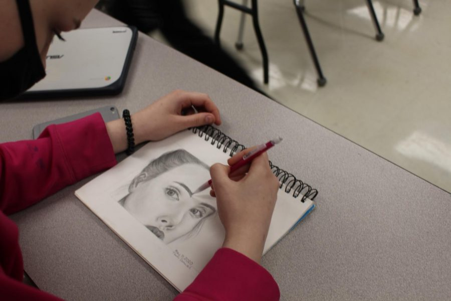 Freshman Tiami Conwell sketches a realistic graphite portrait during class. She is heavily supported by her mom to continue with art, even when things are difficult.
