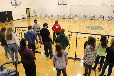 Coach Jackie Downing explains to the archers the safety regulations for archery. Students must wear a mask while they are shooting and stay behind the bow racks when they are done shooting.