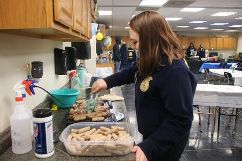 Senior Ellie Wassman grills sausage links in preparation for the FFA Business Appreciation Breakfast. FFA members arrived before school on Feb. 25 to cook breakfast.