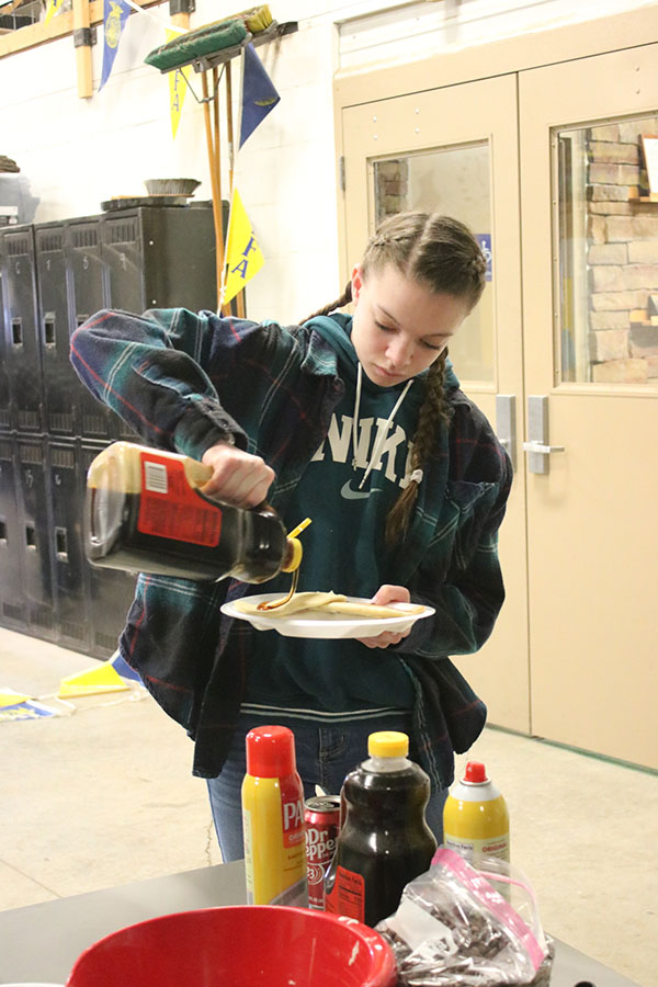 Junior Natalie Johnson pours syrup on her pancakes during