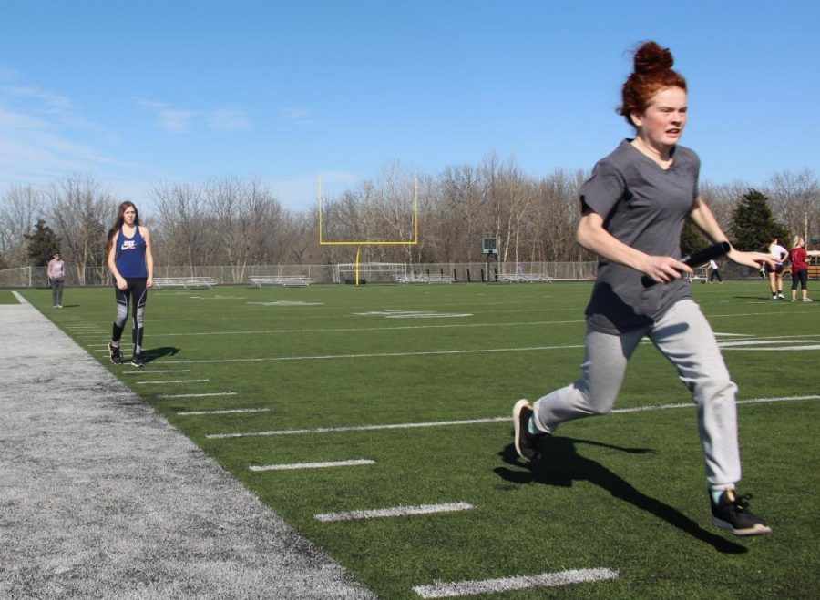 Freshman Hunter Collins takes off after a hand off by sophomore Summer McCannon in relay practice. The track team had their first meet on march 23 at Versailles.