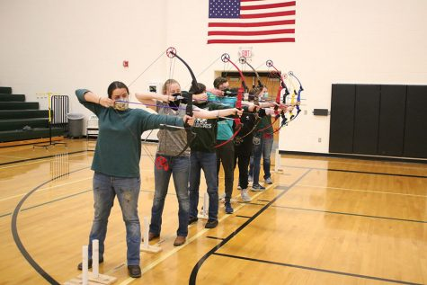 Members of the high school archery team senior Emmaleigh Kowal, sophomore Samantha Pearman, freshman Elliot Kowal, sophomore Logan Schockmann, junior Ryellie Umlauf, junior Alyssa Alcantara and freshman Alyson Alcantara stand at the 10-meter line as they prepare to fire at their targets. The high school team qualified for the state bullseye tournament with their combined score of 3,151.