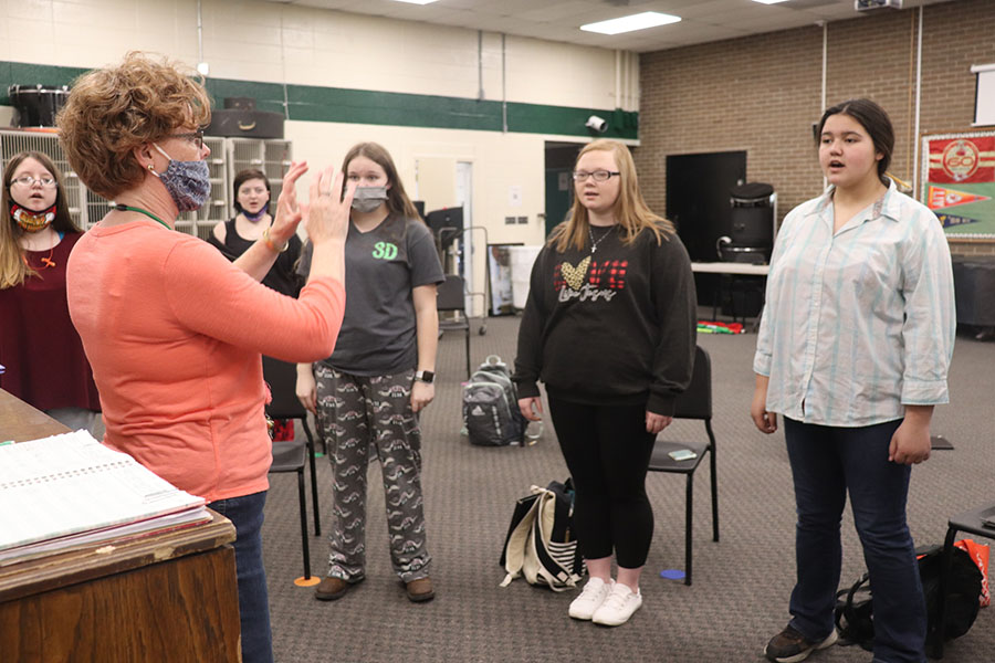 Choir director Deanna Schockmann practices with women's choir members, freshmen Autum Walton, Dallas Steinhoff and Mara Jensen. Choir members must submit their performances digitally for competitions.