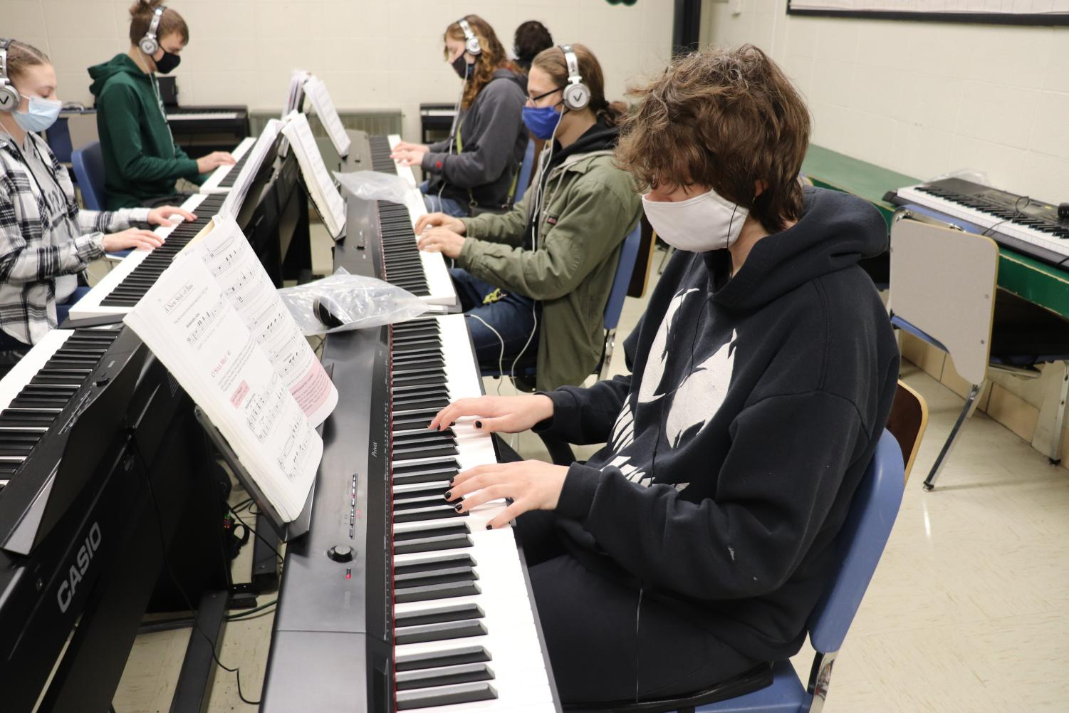 Above: Sophomores Rian Dotson, John Cawood, Jenny Jones, Reece Brazel and junior Natalie Johnson mask up to practice playing piano together.