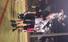 Senior left tackle and defensive end Garrett McGann lifts senior quarterback Brady Slavens to celebrate a touchdown against the El Dorado Springs Bulldogs. The Wildats beat the Bulldogs 50-20.