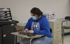 Junior Ashley Spry wears masks while working on school work in Amy Spunaugles math class.